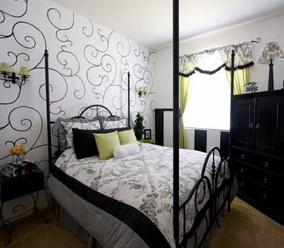 Wide view of smart chic bedroom with curvilinear mural on wall, black and white color scheme, iron bed frame, and dark furniture, and green room highlights.