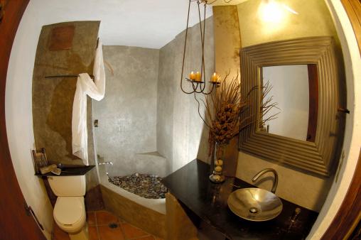 woodland_bathroom_design_stone_shower_pebble_floor_steel_sink_branches_iron_light_fixture_1352849860